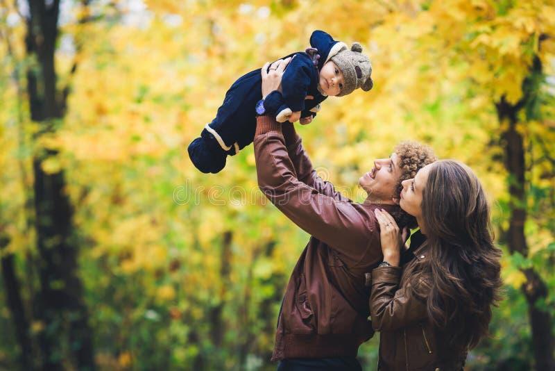 Familia feliz joven en otoño en parque El padre alegre lanza a su hijo para arriba foto de archivo