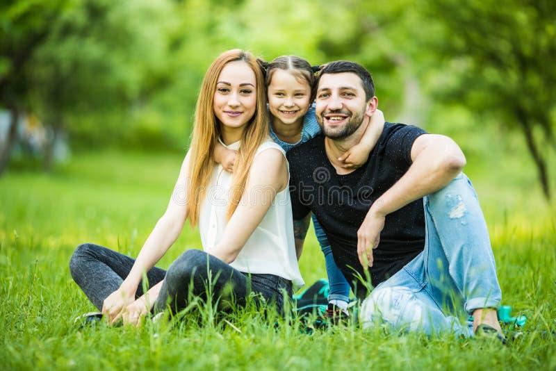 Familia feliz joven en parque del verano El padre y la madre pasan tiempo en parque del verano con su hija fotografía de archivo