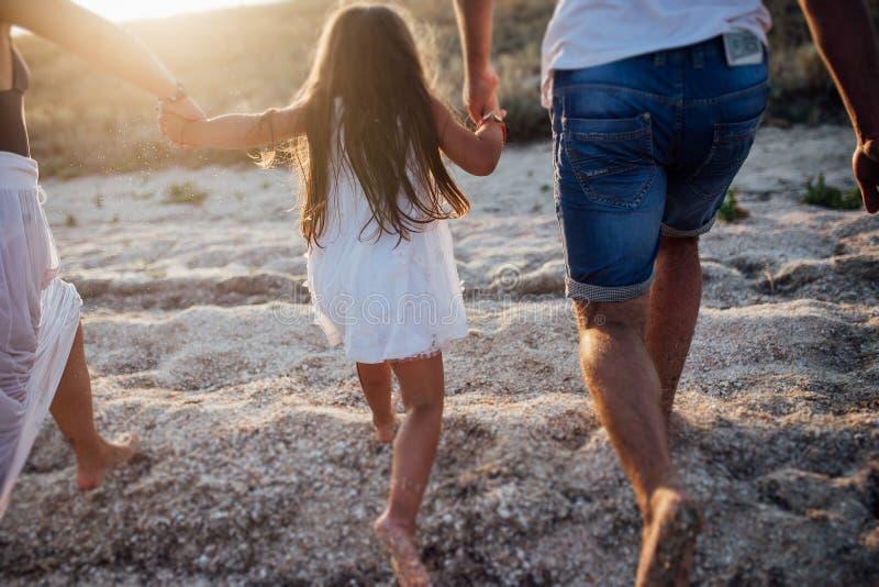 Familia feliz joven que camina a lo largo de la costa fotos de archivo