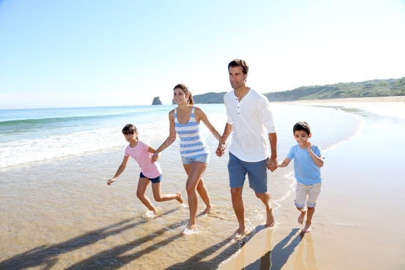 Familia feliz joven que corre en la playa fotos de archivo