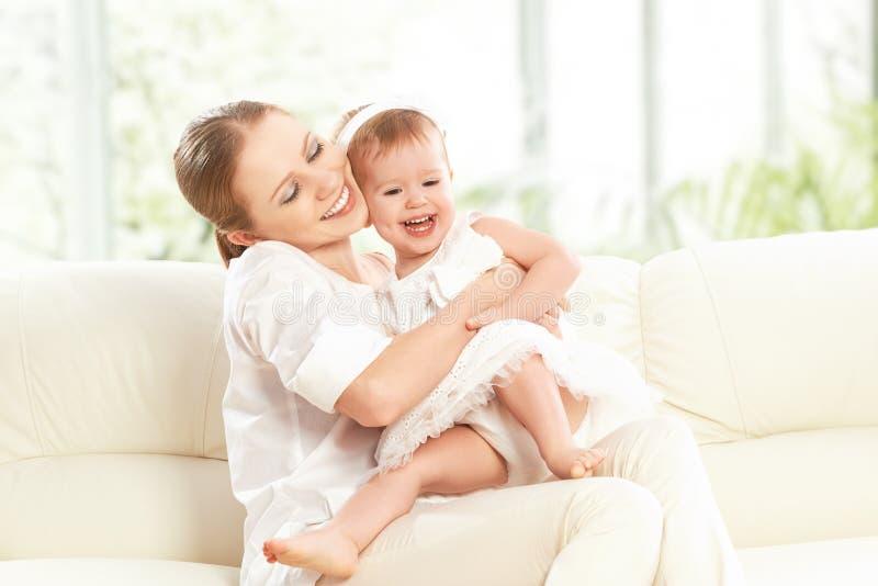 Familia feliz. Juegos de la hija de la madre y del bebé, abrazo, besándose foto de archivo