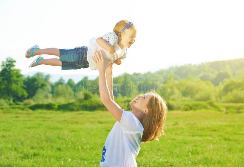 Familia feliz La madre lanza para arriba al bebé en el cielo imágenes de archivo libres de regalías