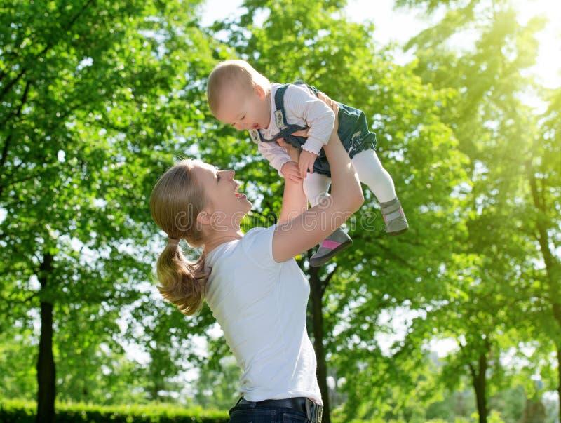 Familia feliz. La madre lanza para arriba al bebé en la naturaleza fotografía de archivo libre de regalías