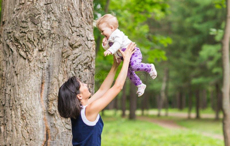 Familia feliz La madre lanza para arriba al bebé, jugando al aire libre foto de archivo libre de regalías