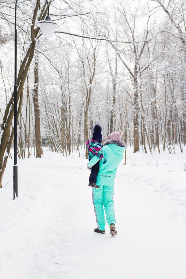 Familia feliz La muchacha de la madre y del niño en un invierno camina en naturaleza fotografía de archivo