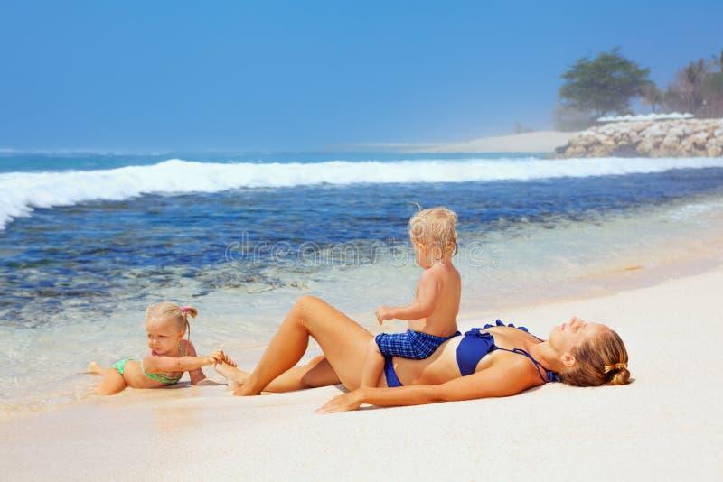 Familia feliz - madre, hijo del bebé, hija que toma el sol en la playa del mar fotos de archivo libres de regalías