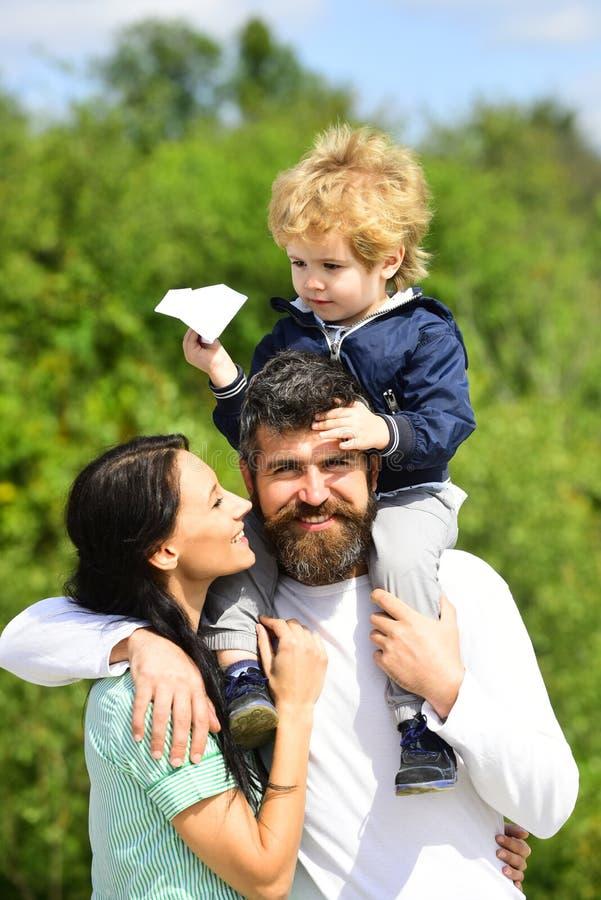 Familia feliz - madre, padre e hijo en fondo del cielo en verano Niño feliz que juega con el avión del papel del juguete contra imagenes de archivo