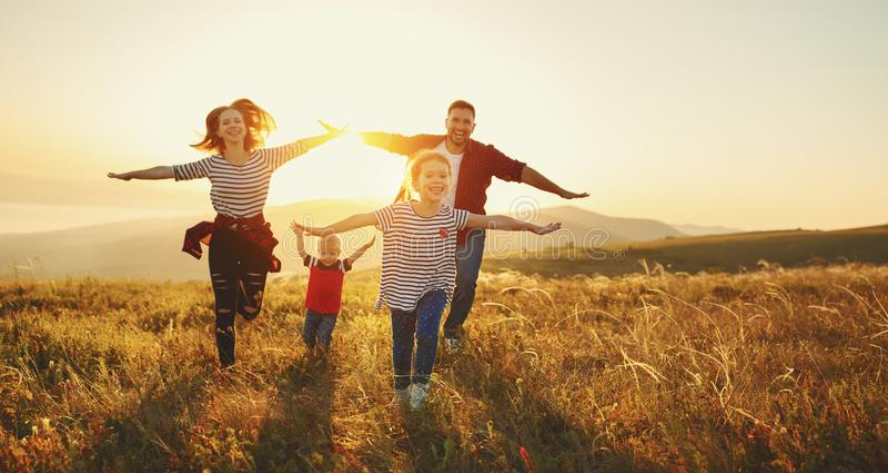 Familia feliz: madre, padre, niños hijo e hija en sunse imagen de archivo libre de regalías