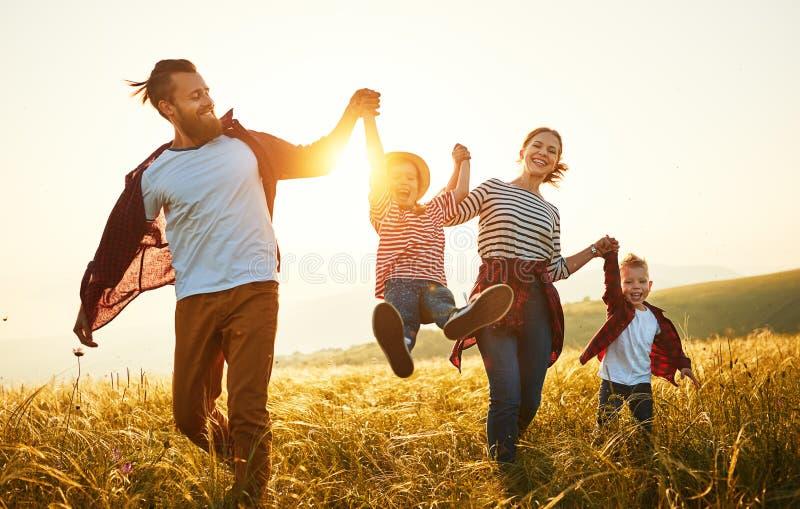 Familia feliz: madre, padre, ni?os hijo e hija en puesta del sol imagen de archivo