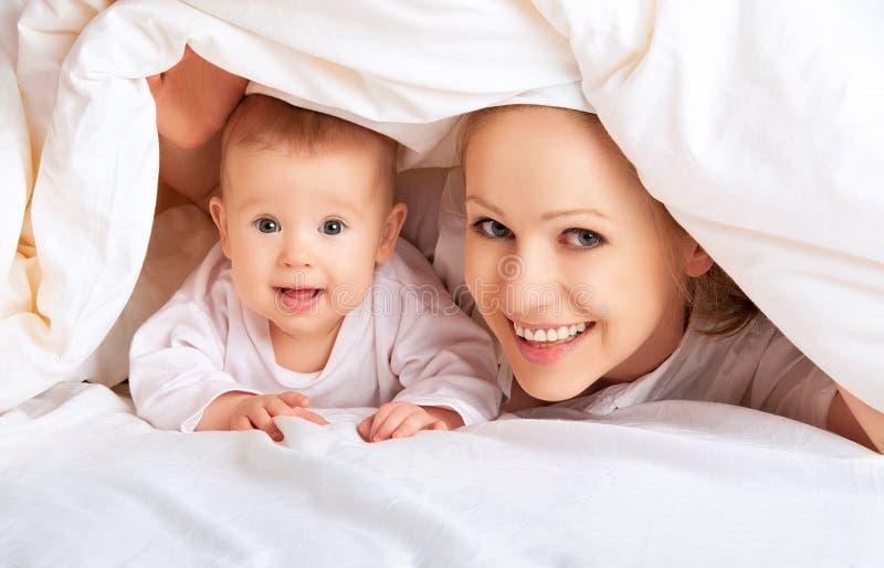 Familia feliz. Madre y bebé que juegan debajo de la manta imagen de archivo