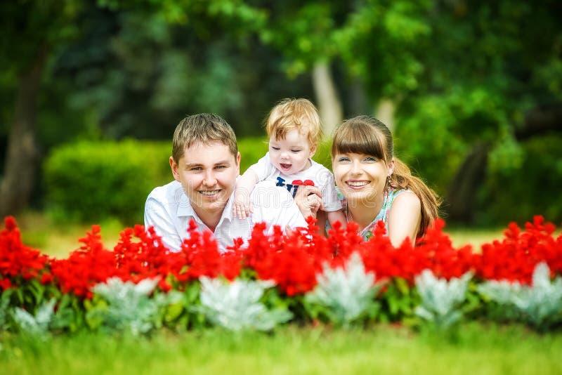 Familia feliz, mamá, papá y pequeño hijo divirtiéndose en el parque Su fotografía de archivo