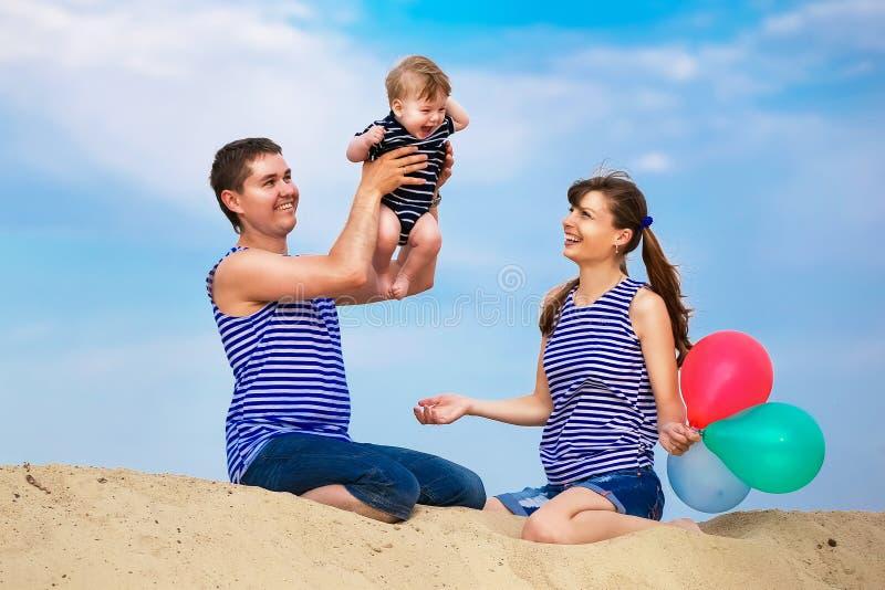 Familia feliz, mamá, papá y pequeño hijo en los chalecos rayados que tienen fu imagen de archivo