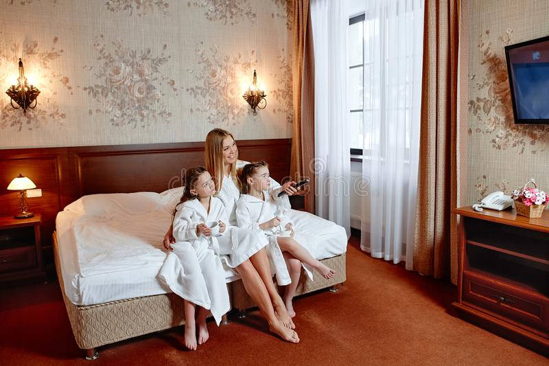 Familia feliz, mamá y dos muchachas gemelas viendo la TV Ellos ` con referencia a sittin fotografía de archivo