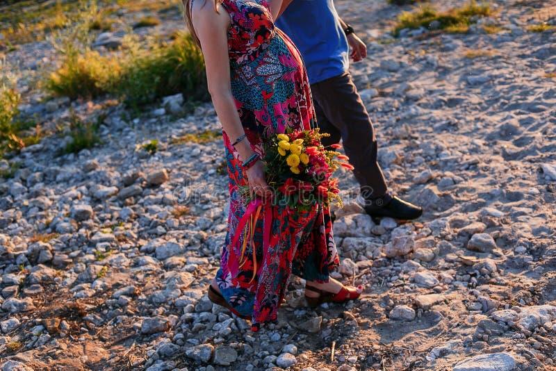 Familia feliz: mujer embarazada hermosa joven, hombre que camina a lo largo de las piedras del mar el día de verano de Sunnset fotografía de archivo