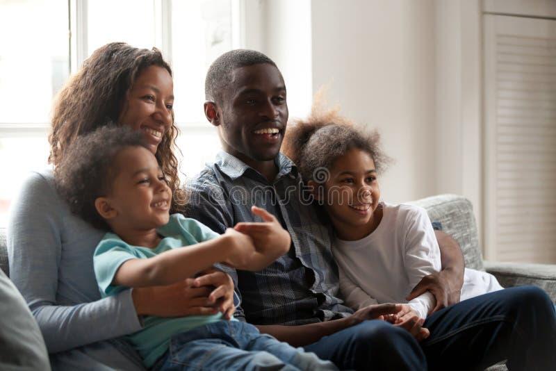 Familia feliz negra junto que se sienta en el sofá en casa imagenes de archivo