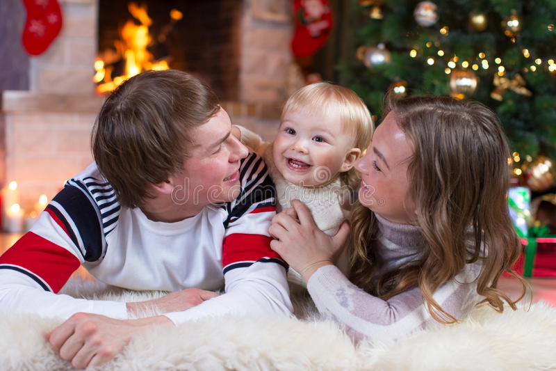 Familia feliz - niño pequeño de la madre, del padre y del bebé que juega en el invierno para los días de fiesta de la Navidad fotos de archivo