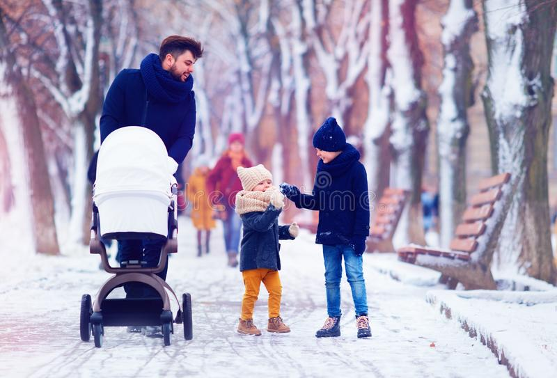 Familia feliz, padre con los niños que caminan en la calle del invierno imagen de archivo libre de regalías