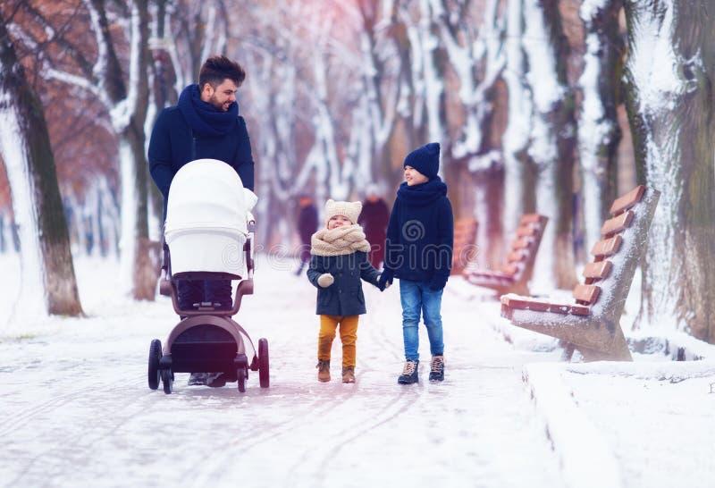 Familia feliz, padre con los niños que caminan en la calle del invierno foto de archivo libre de regalías