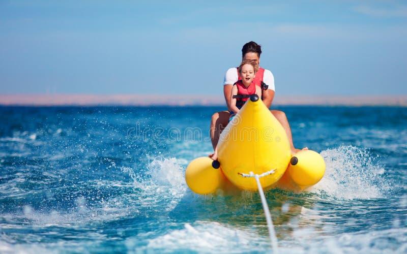 Familia feliz, padre encantado e hijo divirtiéndose, montando en el barco de plátano durante vacaciones de verano fotografía de archivo libre de regalías