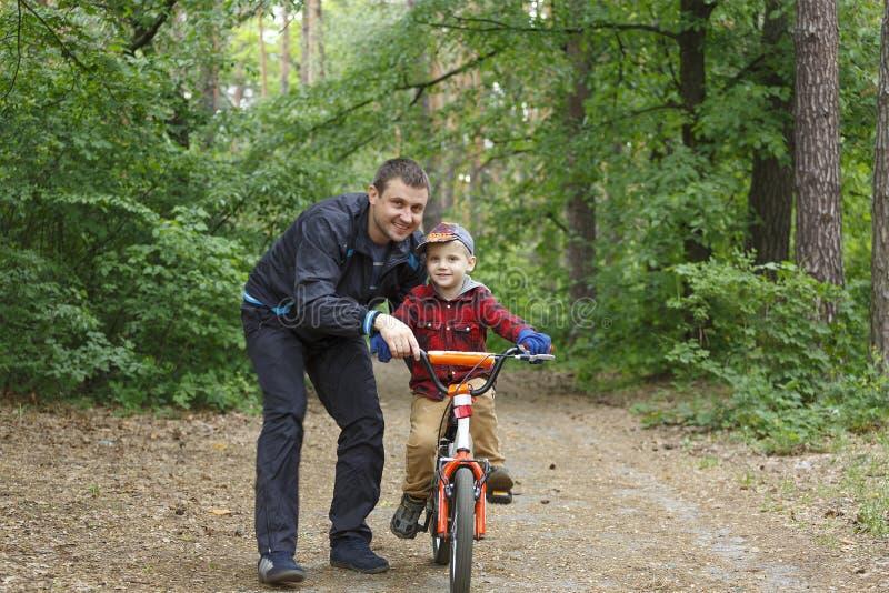 Familia feliz, padre, hijo, diversión, bici, forma de vida, seguridad, deportes, entrenamiento, ocio con concepto de los niños foto de archivo