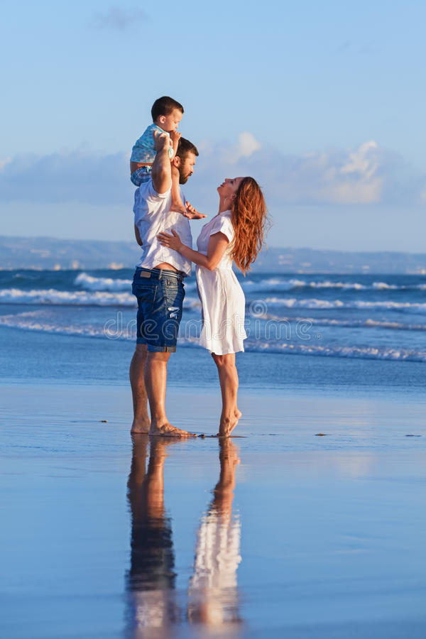 Familia feliz - padre, madre, hijo del bebé el día de fiesta de la playa del mar foto de archivo libre de regalías
