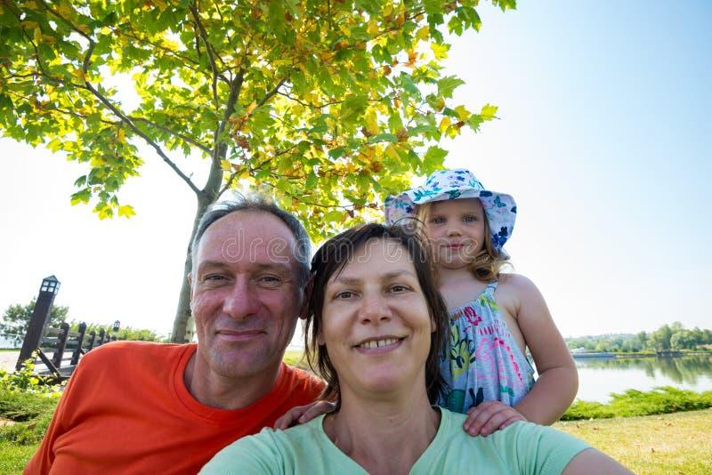 Familia feliz, padres con la pequeña hija, tomando el selfie fotografía de archivo