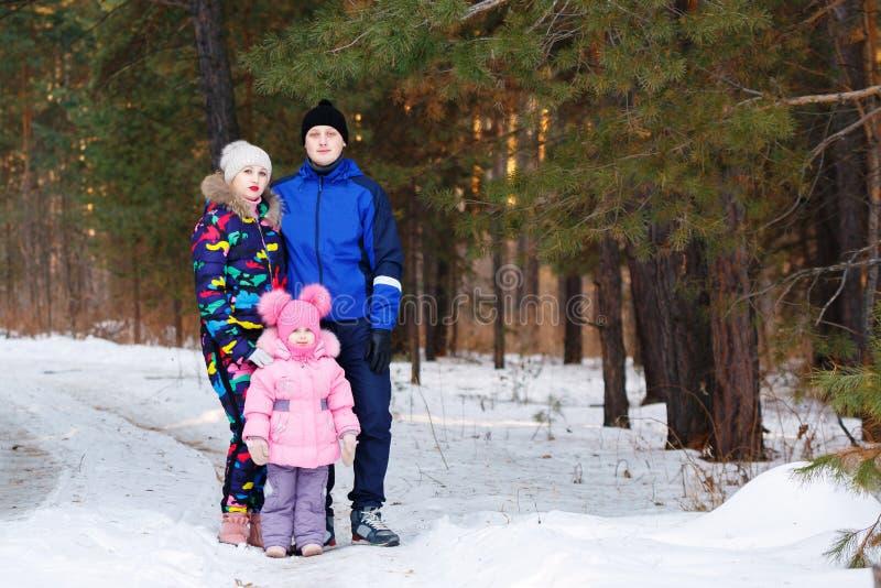Familia feliz, pareja de los jóvenes y su hija pasando el tiempo al aire libre en invierno fotos de archivo libres de regalías