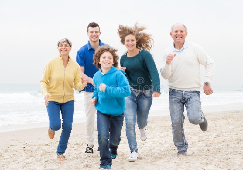 Familia feliz que activa en la playa imagenes de archivo