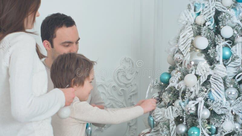 Familia feliz que adorna el árbol de navidad en la sala de estar foto de archivo