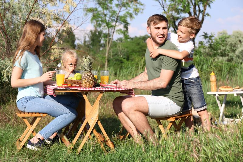 Familia feliz que almuerza en la tabla en comida campestre del verano imagen de archivo