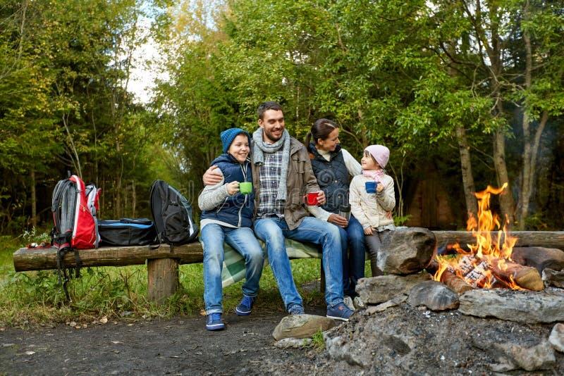Familia feliz que bebe té caliente cerca del fuego del campo foto de archivo