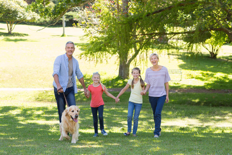 Familia feliz que camina en el parque con su perro fotos de archivo