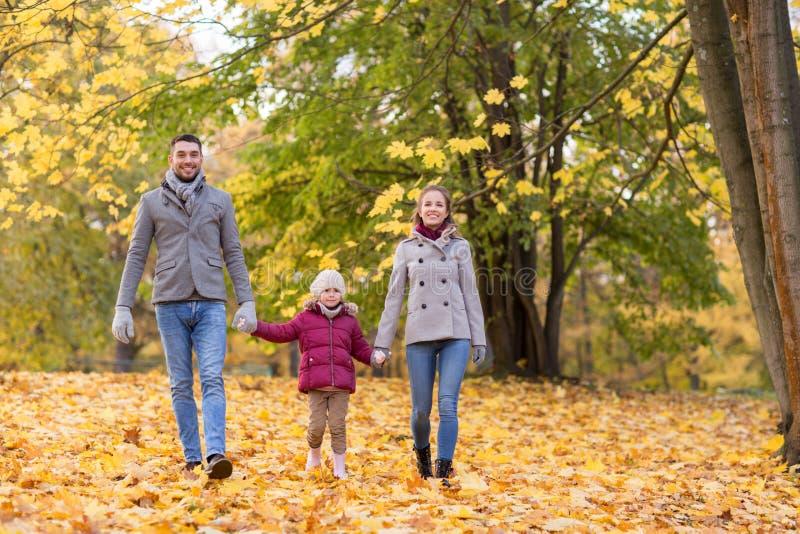 Familia feliz que camina en el parque del otoño fotografía de archivo