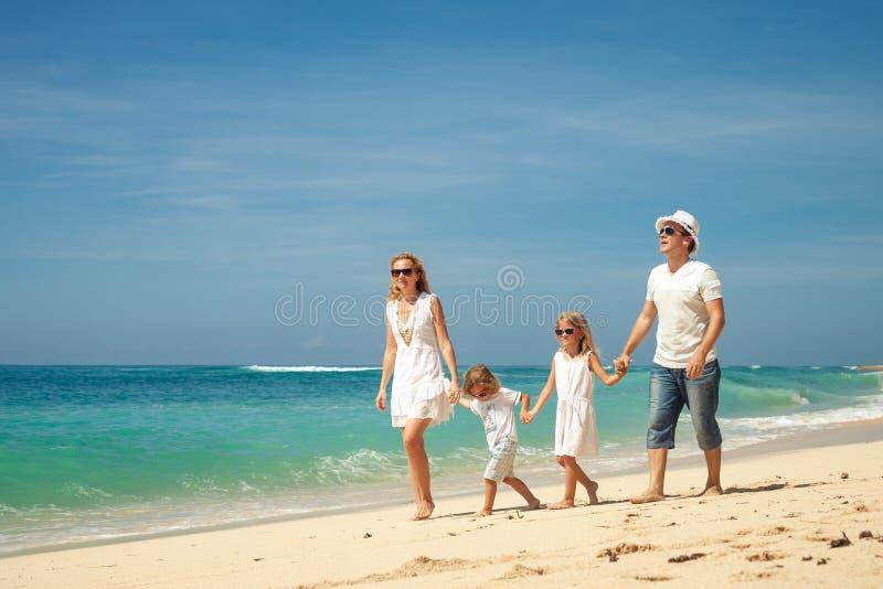 Familia feliz que camina en la playa en el tiempo del día foto de archivo