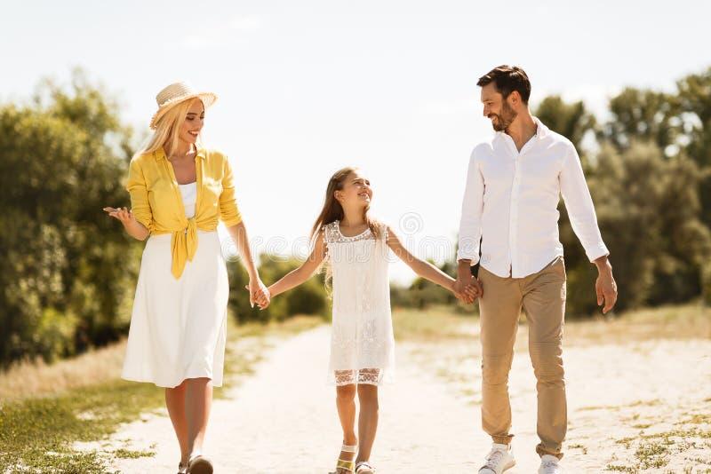 Familia feliz que camina en la trayectoria que lleva a cabo las manos imagen de archivo libre de regalías