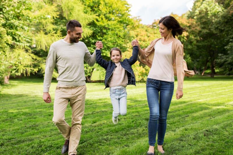 Familia feliz que camina en parque del verano y que se divierte foto de archivo