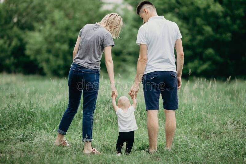 Familia feliz que camina en prado Padres que enseñan a la pequeña hija fotografía de archivo libre de regalías