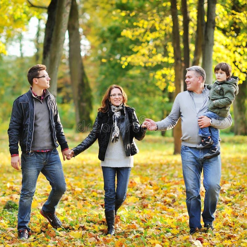 Familia feliz que camina junto en un parque imagen de archivo libre de regalías