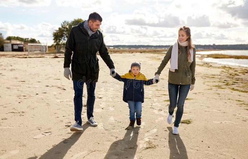 Familia feliz que camina a lo largo de la playa del oto?o foto de archivo