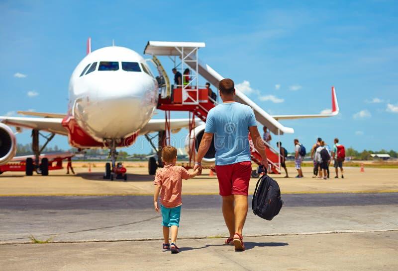 Familia feliz que camina para subir en el avión en aeropuerto, vacaciones de verano imágenes de archivo libres de regalías
