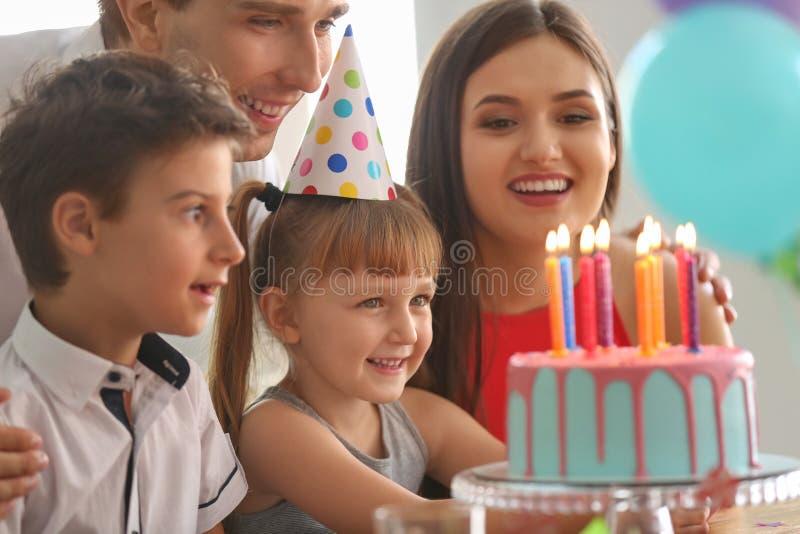 Familia feliz que celebra cumpleaños en el partido fotos de archivo
