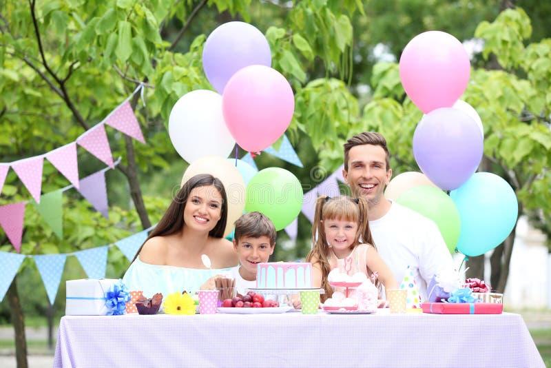 Familia feliz que celebra cumpleaños en la tabla al aire libre imagen de archivo libre de regalías