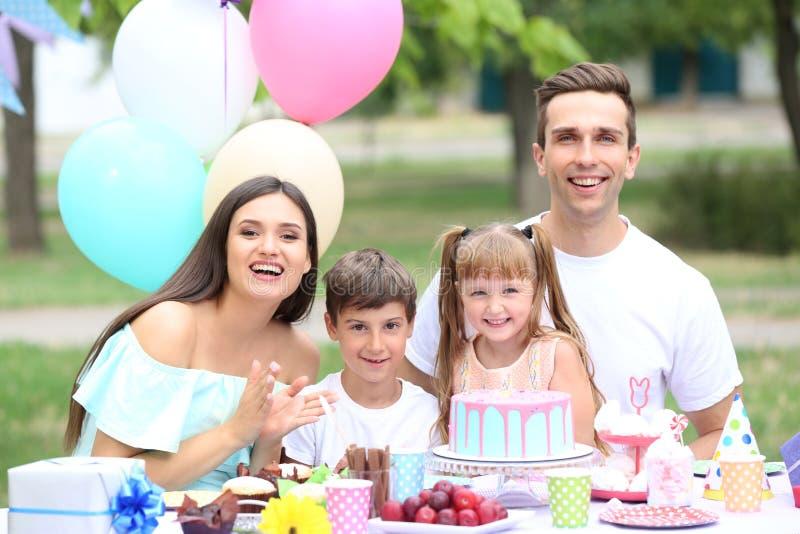 Familia feliz que celebra cumpleaños en la tabla al aire libre imagen de archivo