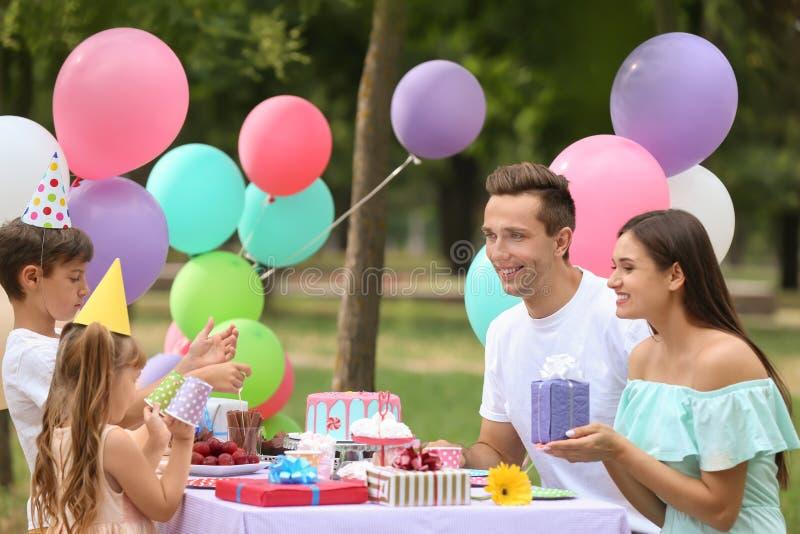 Familia feliz que celebra cumpleaños en la tabla al aire libre imagenes de archivo