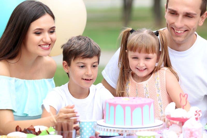 Familia feliz que celebra cumpleaños en la tabla al aire libre fotografía de archivo