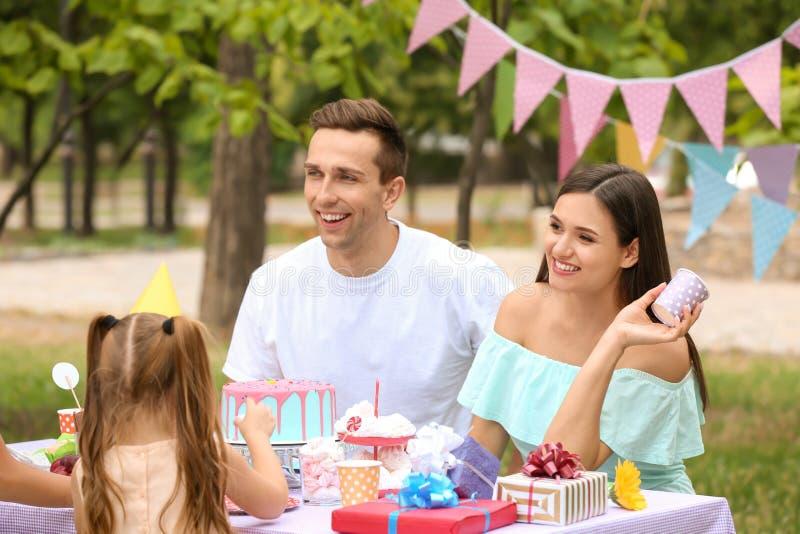 Familia feliz que celebra cumpleaños en la tabla al aire libre foto de archivo libre de regalías