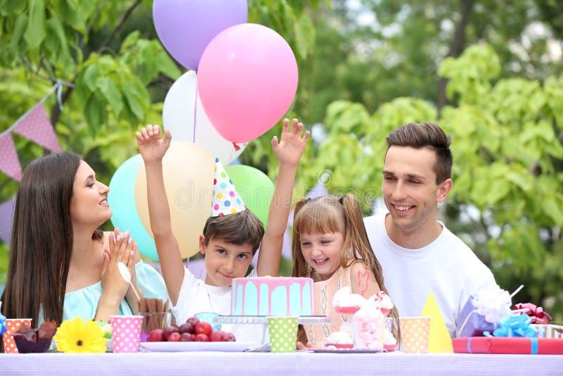 Familia feliz que celebra cumpleaños en la tabla al aire libre fotos de archivo