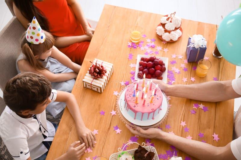 Familia feliz que celebra cumpleaños en la tabla con la torta fotos de archivo