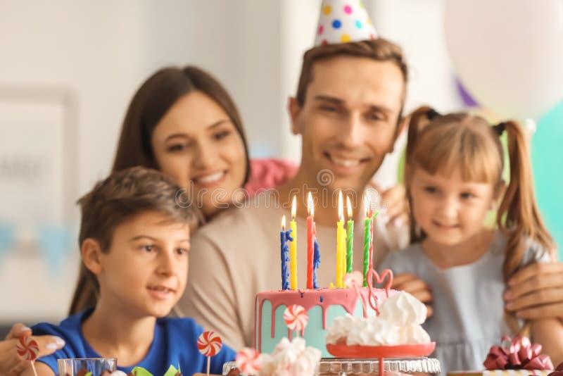 Familia feliz que celebra cumpleaños en la tabla con la torta foto de archivo libre de regalías