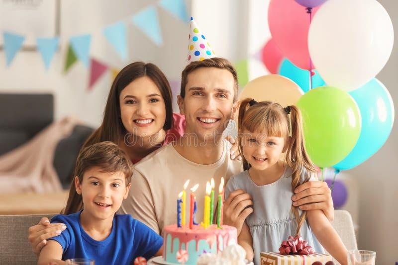 Familia feliz que celebra cumpleaños en la tabla con la torta imagenes de archivo